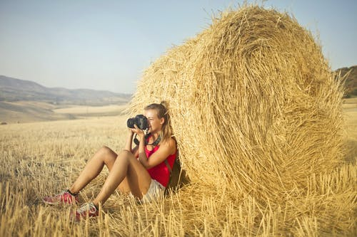 Woman in Red Tank Top and White Shorts Sitting on the Ground Leaning Against a Roll of Hay While Taking a Photo