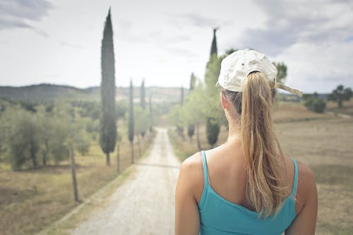 Back View Photo of Woman in Blue Tank Top and White Cap Standing on Dirt Road
