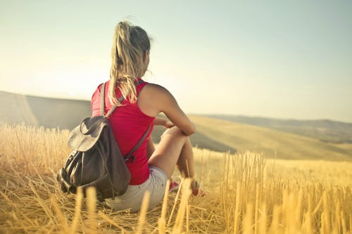 Back View Photo of Woman in a Red Tank Top a Brown Leather Backpack Sitting on Brown Hay Field