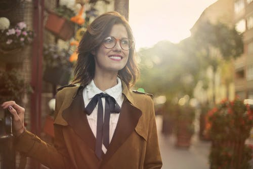 Selective Focus Portrait Photo of Smiling Woman in Brown Coat and Black Framed Eyeglasses Looking Away