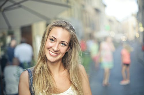 Selective Focus Portrait Photo of Smiling Woman in White Tank Top