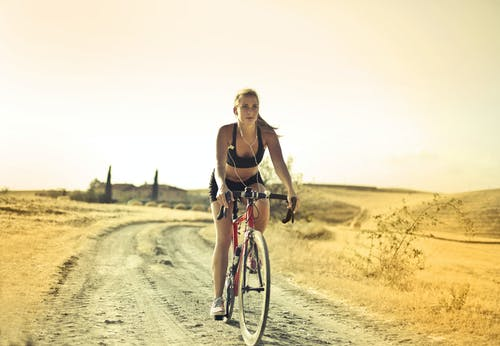 Woman in Black Sports Bra and Shorts Riding Bicycle