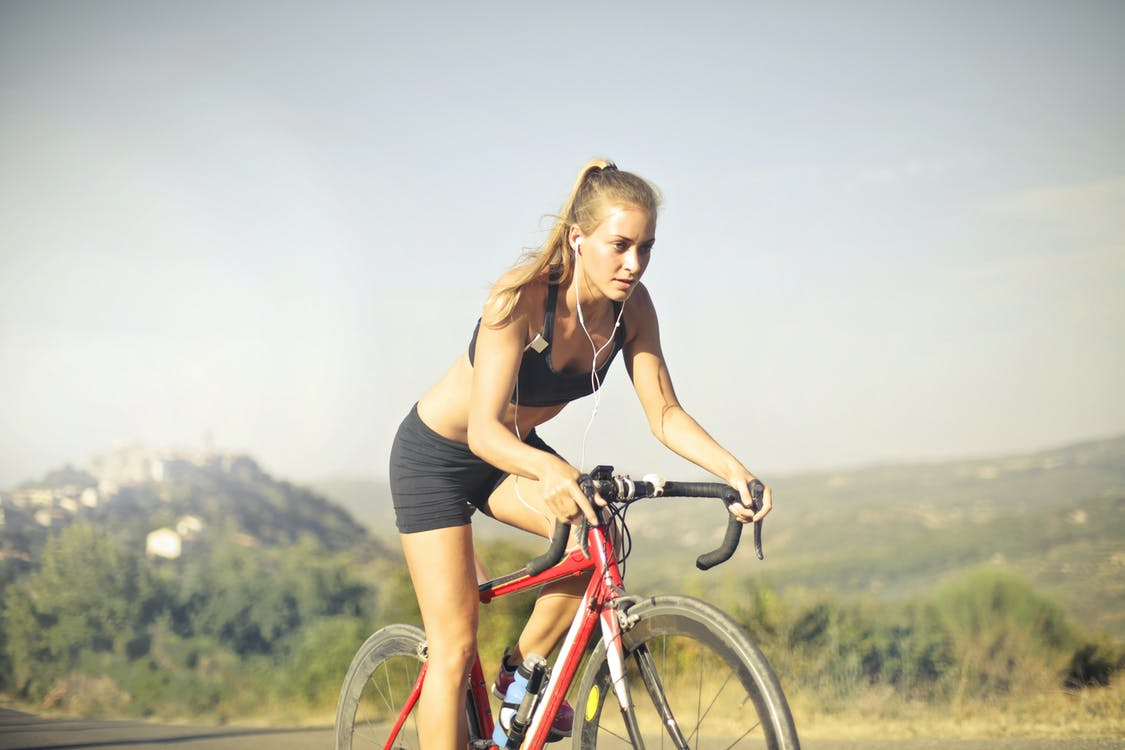 Selective Focus Photo of Woman with Earphones on Riding a Red Bicycle