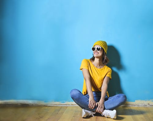 Woman in Yellow Shirt  Sitting on Brown Wooden Floor
