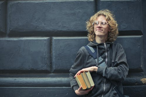 Young Man Leaning Against The Wall Holding A Books
