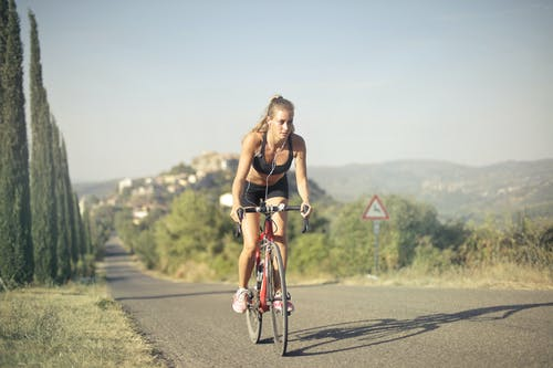 Woman in Black Tank Top Riding Bicycle on Road