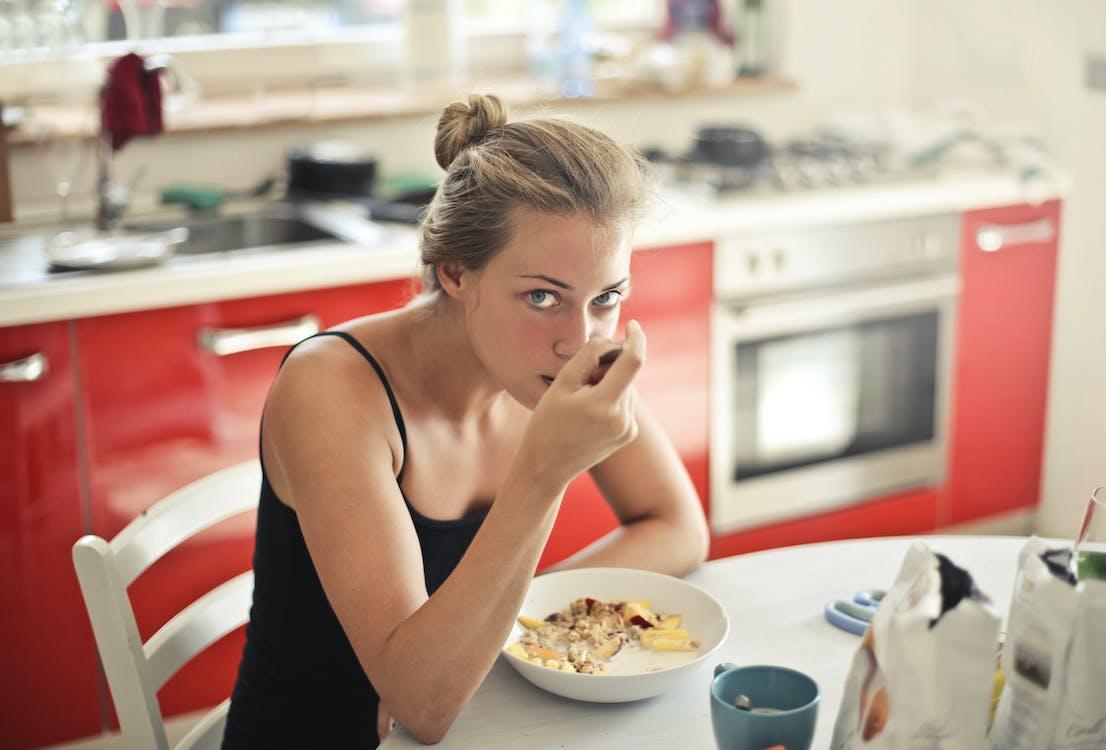 黒のタンクトップのシリアルを食べる女性