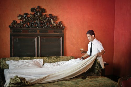 Male servant making bed in luxury hotel room