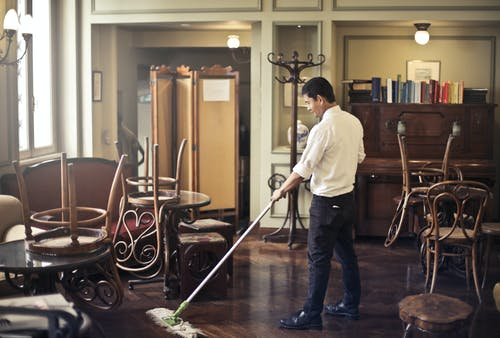 Male employee cleaning floor in restaurant