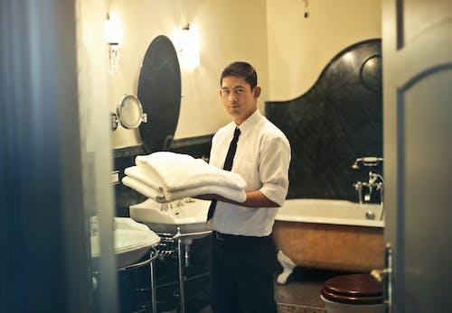 Homme Tenant Des Serviettes De Bain Près De La Baignoire