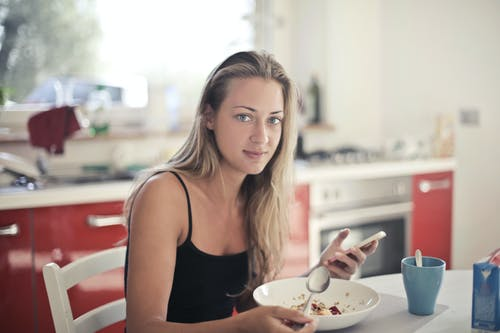 Woman in Black Tank Top Eating Oatmeal