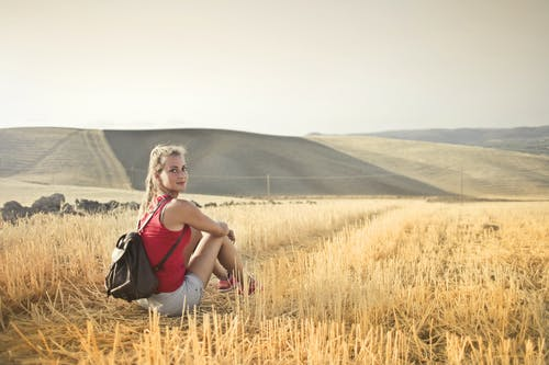 Back View Photo of Woman in a Red Tank Top and a Brown Leather Backpack Looking Back While Sitting on Brown Hay Field