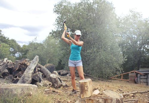 Young woman chopping wood in countryside