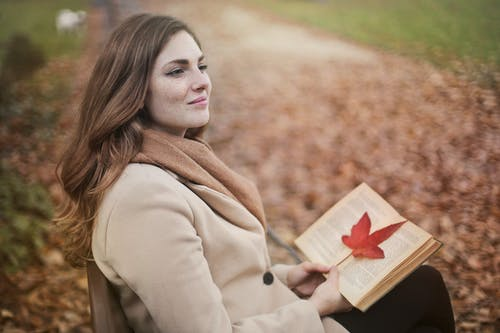 Side view of peaceful young female in warm coat and scarf sitting on bench with open book in hands and looking away pensively while resting in autumn park