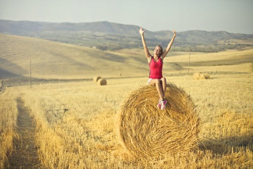 Woman Sitting on Hay Roll