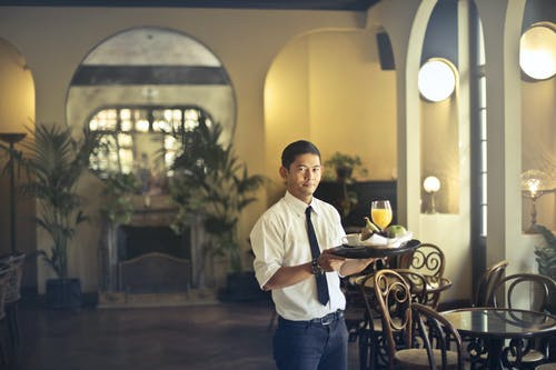 Confident young ethnic waiter in elegant clothes holding tray with food and drinks and looking at camera while serving tables in stylish restaurant