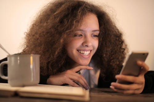 Close-up Photo of Smiling Woman Leaning on Table While Using Her Phone