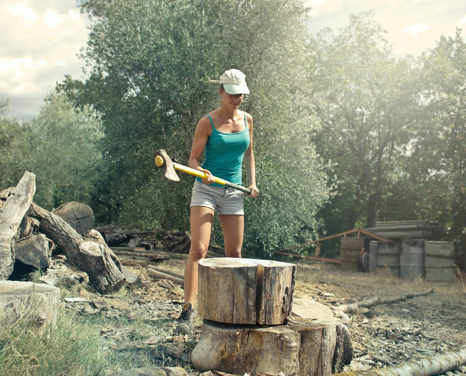 Young female in casual clothes standing in front of large log with axe in hands while chopping wood in backyard of country house in sunny summer day