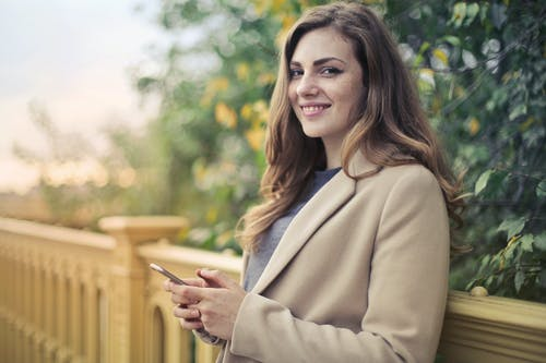 Selective Focus Photo of Smiling Woman in Brown Coat Holding Smartphone While Leaning on stone Railing