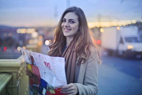 Selective Focus Photo of Smiling Woman Holding a Map while Standing on Bridge Sidewalk