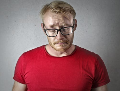 Portrait Photo of a Sad Man in a Red T-shirt and Black Framed Glasses