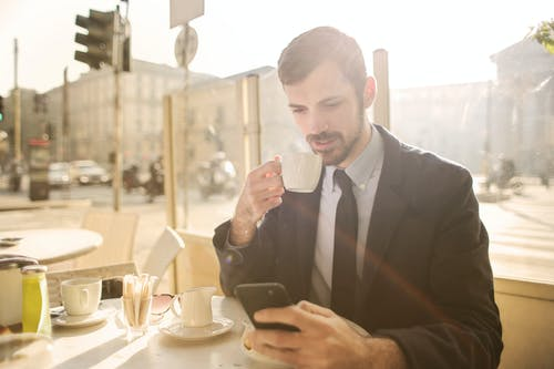 Photo of Man in Black Suit Using His Phone While Drink Coffee at a Cafe