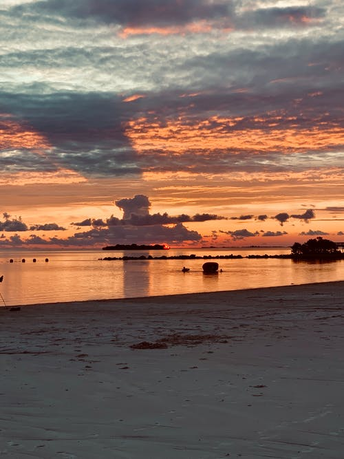 Picturesque scenery of empty sandy beach against cloudy orange sunset sky reflecting on water surface