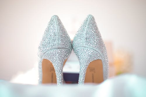 Stylish wedding high heels decorated with shiny silver rhinestones placed on white fabric