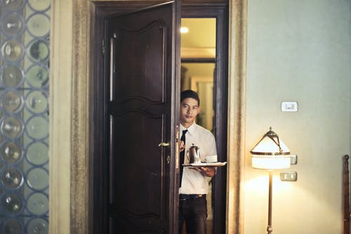Young ethnic male room service waiter carrying tray with coffee pot while entering hotel room with stylish vintage interior