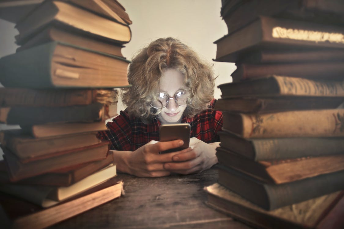 Focused male student in casual wear and glasses browsing smartphone while sitting at wooden table with stacked old books