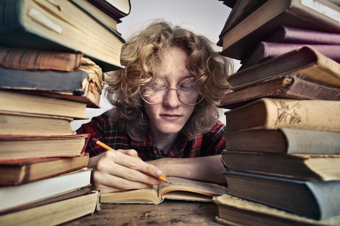 Close-up Photo of Person in Glasses Reading Books