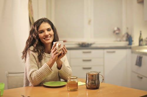 Selective Focus Photo of Smiling Woman in Beige Knit Sweater Holding White Ceramic Mug