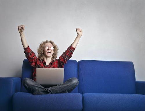 Foto Van Opgewonden Persoon Met Handen Omhoog Zittend Op Een Blauwe Bank Tijdens Het Gebruik Van Een Laptop