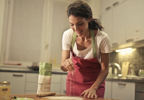 Low angle of positive young female in apron sprinkling flour over table while preparing food in modern light kitchen
