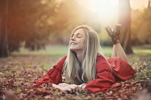 Woman in Red Dres Lying on Ground With Dried Leaves
