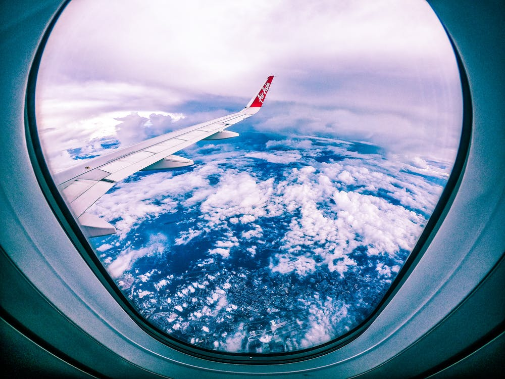 Wide angle of rocky ground through cloudy sky and plane wing from window of aircraft