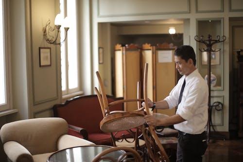 Male employee preparing tables in restaurant