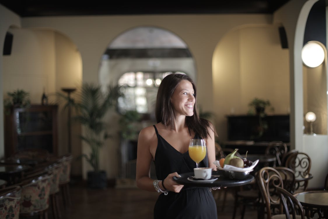 Happy woman carrying tray with breakfast in hotel restaurant