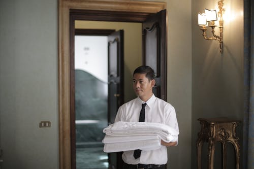Hotel staff with bed linen