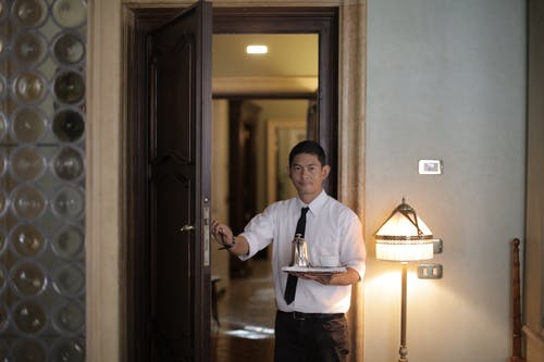 Friendly ethnic male waiter serving clients in room and carrying tray with coffee while working in stylish hotel