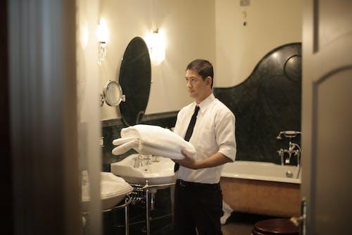 Male servant preparing bathroom in hotel