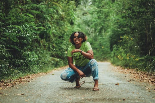 Photo of Smiling Woman in Green T-shirt and Blue Denim Jeans Squat Posing on Paved Trail