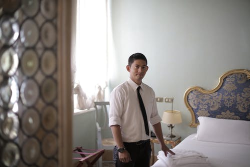 Young ethnic male attendant standing next to bed with stacked linen in stylish hotel room and looking at camera