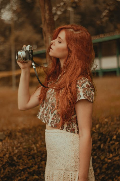 Woman in White and Orange Floral Tank Top Holding Camera