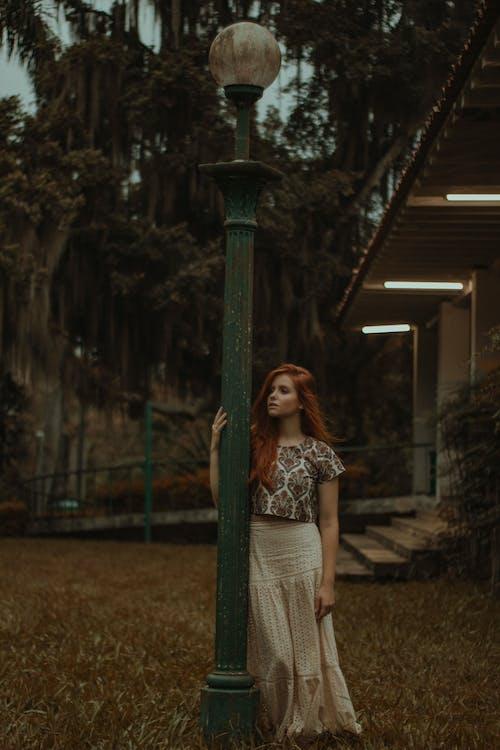 Woman In Crop Top Shirt Standing Beside Lamp Post