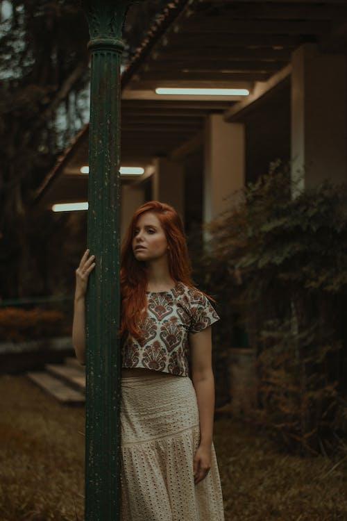 Woman Wearing Floral Shirt Standing Near Green Post