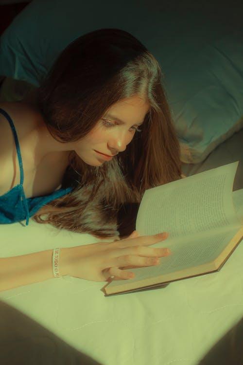 Woman in Blue Spaghetti Strap Top Reading Book