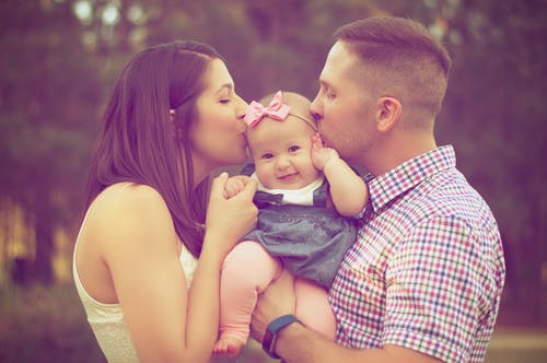 Couple Kissing Baby While Carry baby attachment to both parents