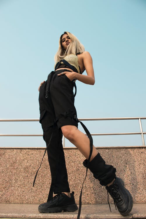 Low Angle Photo of Posing Woman in Black Pants and Golden Top Looking Down