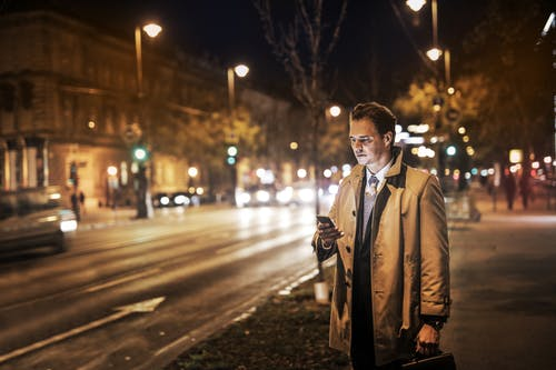 Photo of Man in Brown Overcoat Carrying a Briefcase and Standing on Sidewalk at Night While Using His Phone